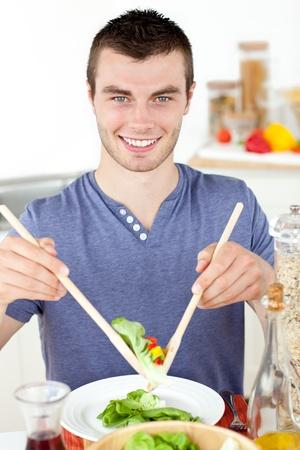 Joven guapo comiendo una ensalada sonriendo a la cámara en la cocina Foto de archivo - 10247650