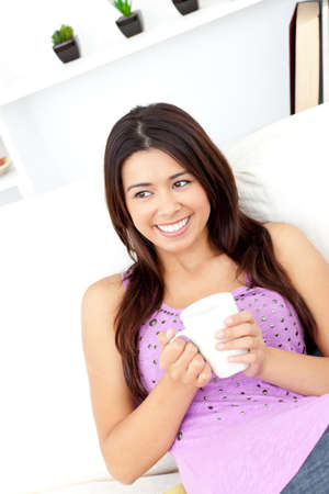 captivation: Relaxed woman holding a cup of coffee sitting on the sofa  Stock Photo