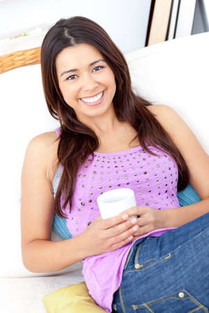 captivation: Bright woman holding a cup of coffee smiling at the camera  Stock Photo