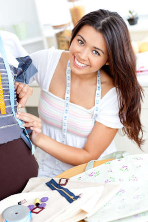 Pretty asian woman sewing at home photo