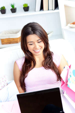 Cheerful asian woman using her laptop after shopping on the sofa  photo