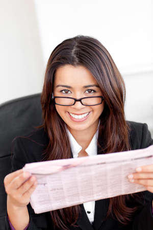 Charming asian businesswoman holiding a newspaper smiling at the camera  Stock Photo - 10249801