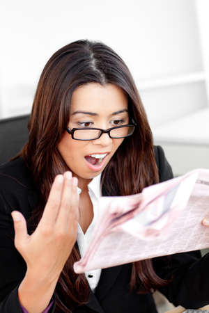Shocked asian businesswoman looking at the newspaper in her office photo