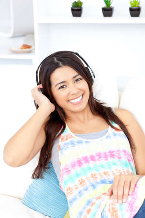 radiant: Radiant asian young woman listen to music with headphones on the couch smiling at the camera
