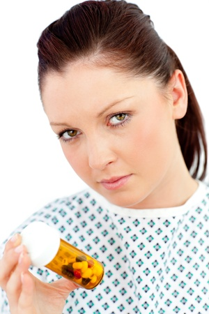 Depressed sick woman holding pills looking at the camera photo