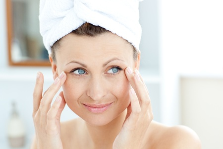 Smiling young woman putting moisturizer on her face Stock Photo - 10249846