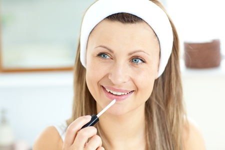Attractive young woman using lipgloss in the bathroom photo