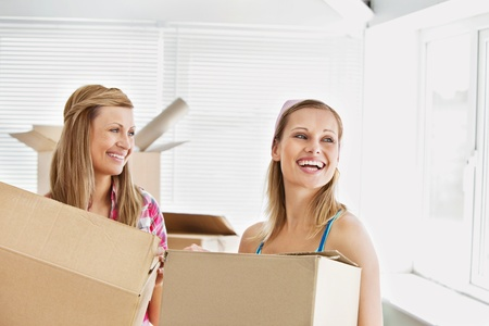 Laughing female friends holding boxes after moving  photo