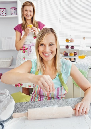 Animated female friends baking muffins smiling at the camera photo
