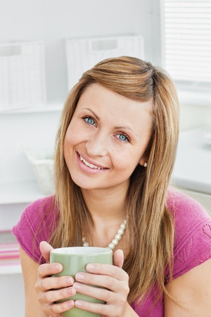 Portrait of a captivating woman holding a cup smiling at the camera  photo