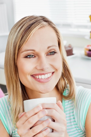 Portrait of a relaxed woman holding a cup of coffee photo