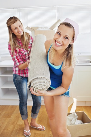 Delighted women holding a carpet standing in the kitchen photo