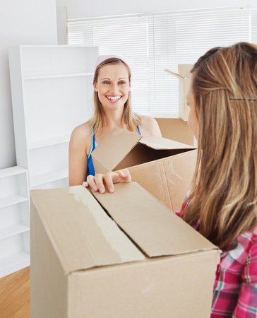 Two radiant female friends holding boxes after moving photo