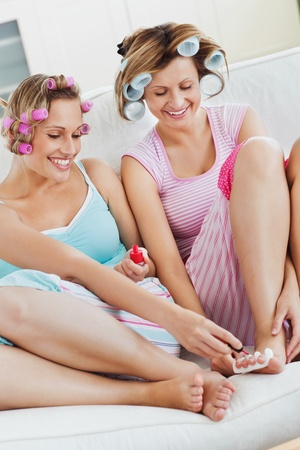 toenail: Positive female friends doing pedicure and wearing hair rollers