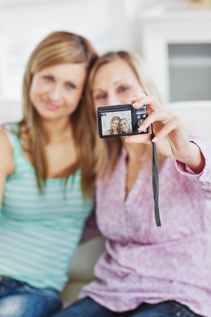 Close female friends taking pictures of themselves with a digital camera Stock Photo - 10249910