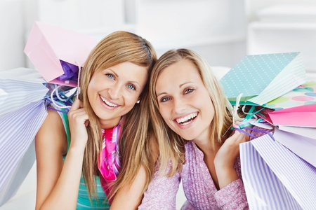 Glowing two women holding shopping bags smiling at the camera photo