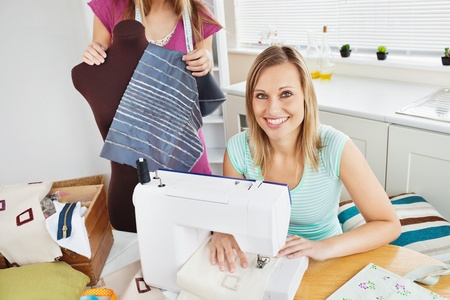 Smiling woman sewing in the kitchen with her friend photo