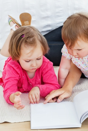 Concentrated children reading a book with their mother Stock Photo - 10249842