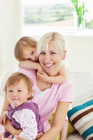 Niñas sonrientes abrazando a su madre Foto de archivo - 10249926