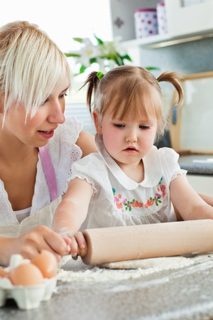 Attentive young mother baking with her daughter photo