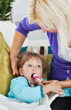 bedridden: Sick little girl getting syrup from her caring mother  Stock Photo