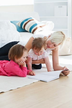 Positive young family reading a book on the floor  photo