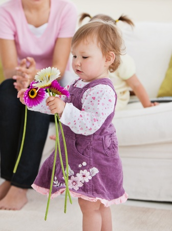 Adorable little girl holding flowers in the living-room  Stock Photo - 10246215