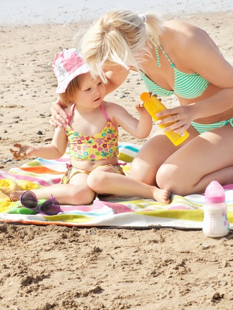 Attentive mother at the beach with her daughter  photo