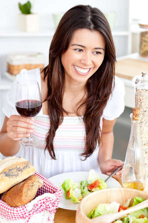 Captivating asian woman holding a wineglass eating a salad at home photo