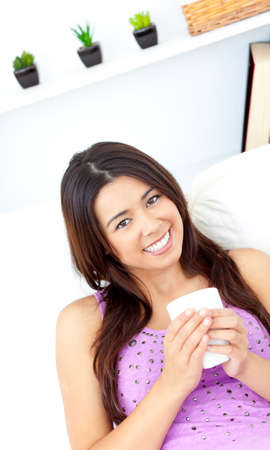 Pretty asian woman holding a cup of coffee at home photo