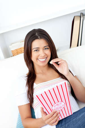 Cheerful asian woman eating popcorn  photo
