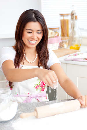 Lively asian woman baking in the kitchen photo