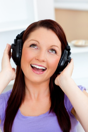 Singing young woman listening to music  photo