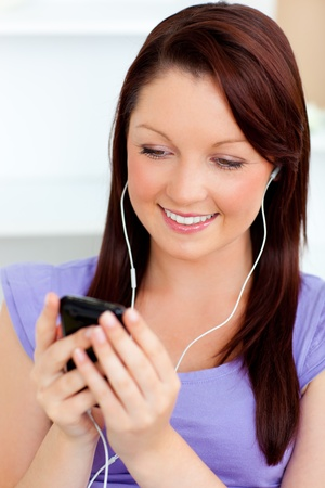 Charming woman listen to music using her cellphone photo