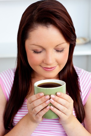 Relaxed young woman enjoying her coffee  photo