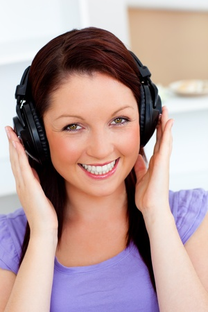 Smiling pretty woman listen to music with headphones looking at the camera photo