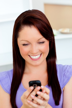 delighted: Delighted young woman sending a text  Stock Photo