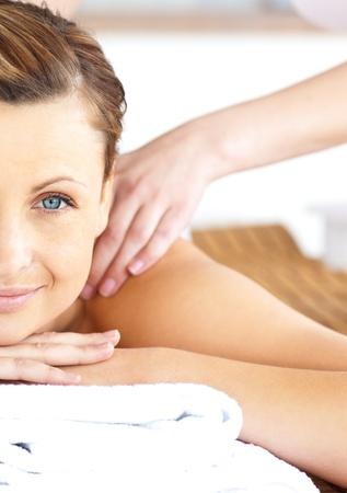 masoterapia: Primer plano de una hermosa mujer que recibir un masaje de espalda mirando la cámara Foto de archivo