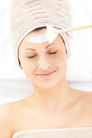 Happy relaxed woman receiving white cream on her face Stock Photo - 10249867