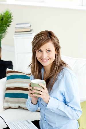 Attractive businesswoman drinking coffee using her laptop sitting on a sofa photo