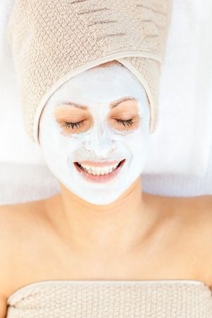 Merry young woman with white cream on her face relaxing on a massage table  photo