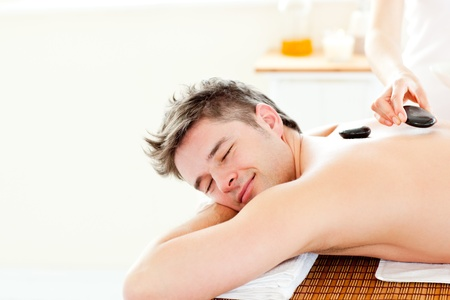 Smiling young man enjoying a back massage with hot stones Stock Photo - 10246476