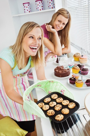 Laughing woman baking together photo