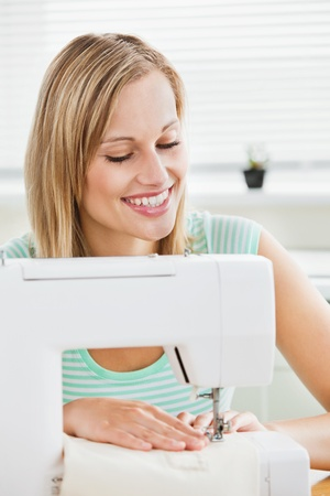 Portrait of a smiling woman sewing clothes at home  photo