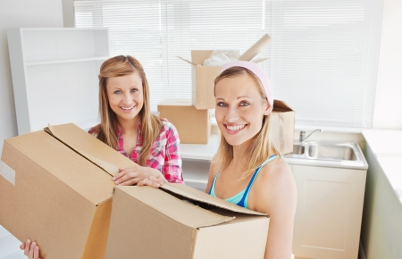Bright female friends holding boxes  photo