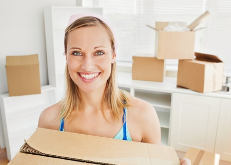 Smiling woman holding boxes after moving  photo