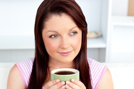 Caucasian woman holding a cup of coffee at home photo