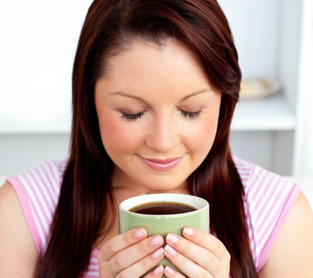 Delighted woman holding a cup of coffee at home Stock Photo - 10246517