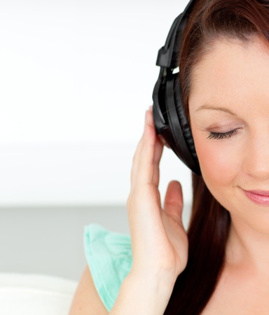 Delighted woman listening to music with headphones at home photo