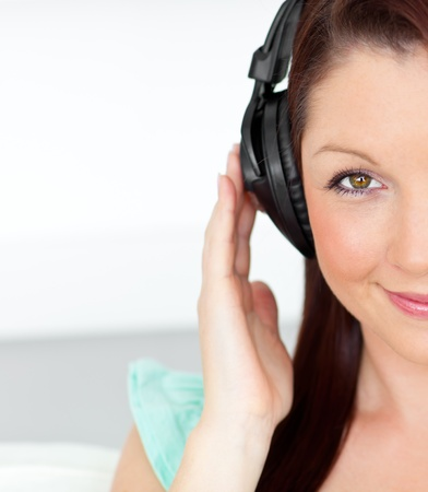 Pleased woman listening to music with headphones at home photo